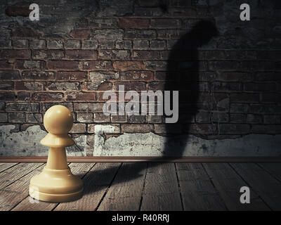 A white pawn piece into a dark room with its man silhouette shadow on a brick wall - Stock Photo