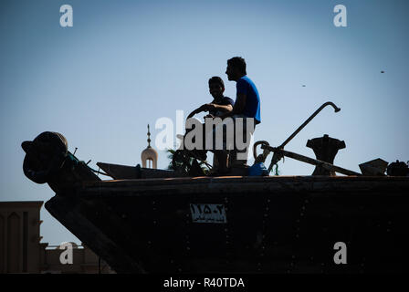 Two men sitting on a boat in the Creek in Dubai - Stock Photo