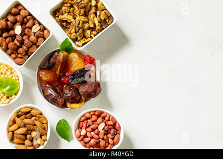 Various Nuts in a ceramic bowl and Dried Fruits on a light stone table. The Concept of a Healthy Dessert. Top view flat lay background. Copy space. - Stock Photo