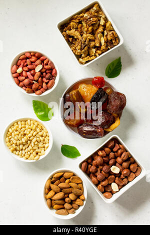 Various Nuts in a ceramic bowl and Dried Fruits on a light stone table. The Concept of a Healthy Dessert. Top view flat lay background. - Stock Photo