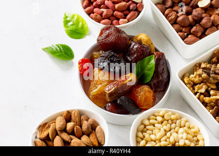 Various Nuts in a ceramic bowl and Dried Fruits on a light stone table. The Concept of a Healthy Dessert. - Stock Photo