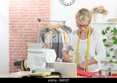 blonde woman in a sewing workshop - Stock Photo
