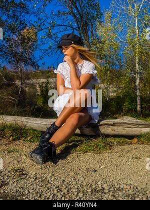 Attractive teen girl adolescent sitting on wooden log in forest looking aside away concerned serious negative feeling forest Green in background - Stock Photo