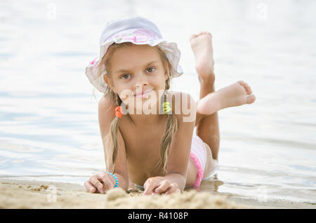 Six year old girl lying on the sand on the beach - Stock Photo