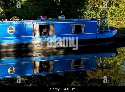 Man making phone-call on narrowboat, Grand Union Canal, near Marsworth, Buckinghamshire, England UK - Stock Photo