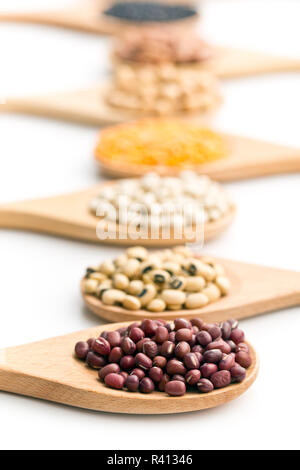 various dried legumes in wooden spoons - Stock Photo