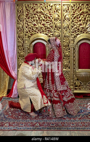 A Sikh bride and groom pose for their wedding photographer in a temple after their wedding ceremony. In Queens, New York City. - Stock Photo