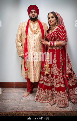 A Sikh bride and groom pose for a full length portrait in a temple after their wedding ceremony. I Queens, New York City. - Stock Photo