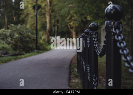 Moody, Dark Photo of the Road in a Park, Between Woods - Closeup view of the Chain Fence with Blurred Background - Desaturated, Vintage Look with Spac - Stock Photo