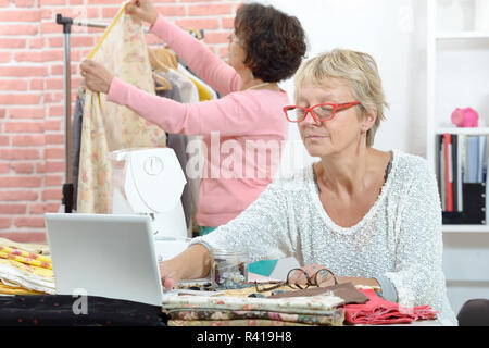 Two cheerful  seamstresses working together in their workshop - Stock Photo
