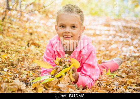 Six year old girl lying on the yellow fallen leaves - Stock Photo