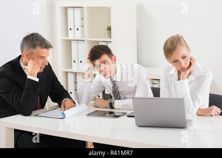 Businesspeople Getting Bored In Office - Stock Photo