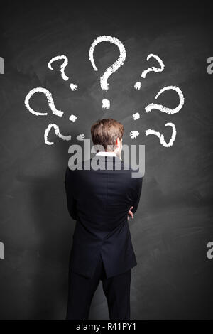 businessman having many questions symbolized as questionmarks on a blackboard over his head - Stock Photo