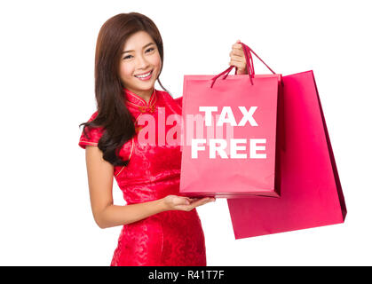 Chinese Woman hold with red paper bag and showing tax free - Stock Photo