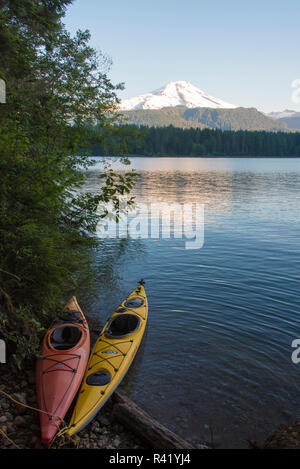 USA, Washington State. Kayaks tethered at edge of Baker Lake with Mt. Baker reflected in calm morning light - Stock Photo