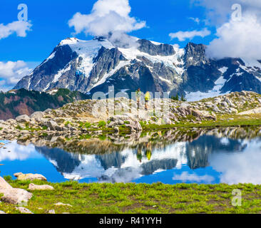 Hikers on Mount Shuksan. Pool reflection on Artist Point, Mount Baker Highway, Washington State, USA - Stock Photo
