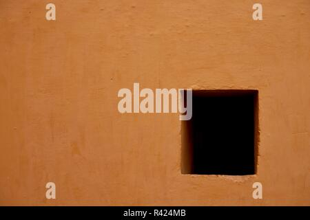 Textured brown wall with empty dark window in the Thar Desert near Jaipur, Rajasthan, India. - Stock Photo