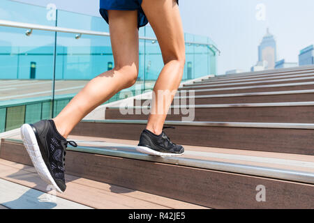 Sporty girl stepping on the staircase - Stock Photo