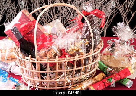 Christmas hamper basket with cookies, chocolate Santa and a bottle of wine - Stock Photo