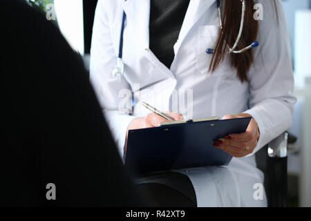 Female doctor hand hold silver pen - Stock Photo