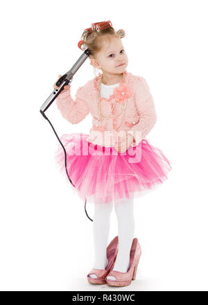 Little girl with curling iron. - Stock Photo