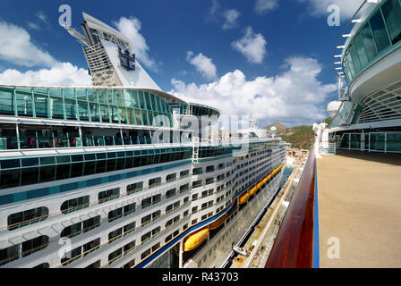 A view of Royal Carirbbean's Explorer of the Seas as viewed from the upper deck of the Adventure of the Seas, docked at St. Maarten. - Stock Photo