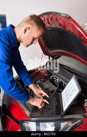 Mechanic Fixing Car With The Help Of Laptop - Stock Photo