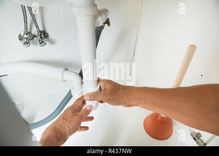Plumber Working On Pipes Under Kitchen Sink - Stock Photo