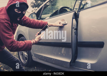 Closeup view of carjacker trying to open car with pick-lock. Masked man squats and breaks someone's car looking to the viewer. - Stock Photo