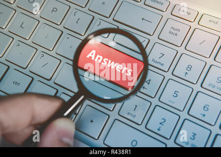 Button Answers on laptop keyboard viewed through the magnifier hold by male hand. Key answers on modern keyboard background. Searching for answers in internet. Finding answers to guestions online - Stock Photo