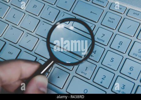 Blank button of laptop keyboard magnidied through the magnifying glass. Wordless key of a computer keypad viewed through the loupe. Write your text on computer keyboard. Concept of internet surfing. - Stock Photo