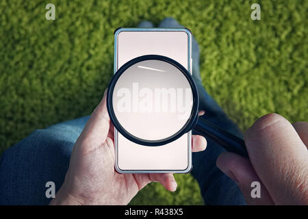 Top-down view to sitting man with blank smartphone and magnifying glass above its screen. Man holds magnifier to find something in mobile internet. Use of cell phone for searching information online. - Stock Photo