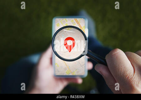 Shot of male hands holding magnifying glass with the red icon of geo-location and looking through it to the smartphone with online city map on the screen. Concept of using mobile net for navigation. - Stock Photo