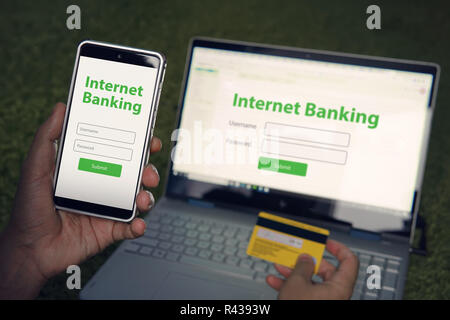 Man browsed homepage of internet banking service on his smartphone and laptop holding credit card. Online payment mobile banking concept. Written words Internet banking on phone and notebook screens. - Stock Photo