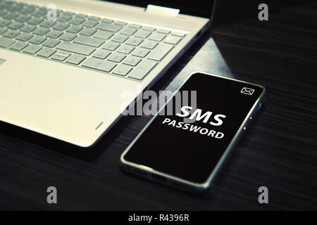Table with open laptop and black-screened smartphone with white written words SMS password on its display. Concept of linking the work of computer and mobile via sms password entering. One time code. - Stock Photo