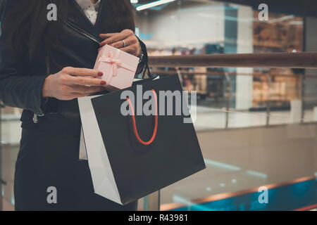 gift bags in the hands of the girl, on the background, Shopping Mall. shopping, gifts, sale, New Year's shopping. Woman puts a gift box in a black package. - Stock Photo