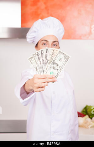 wad of dollar banknotes in woman chef hand - Stock Photo