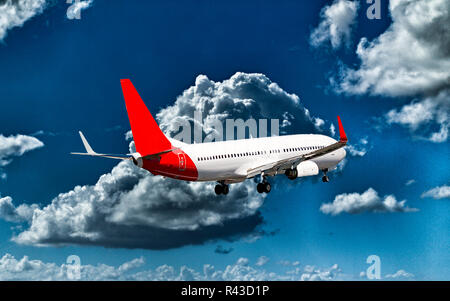 A passenger jet aircraft flyng in a vibrant blue sky, with well developed bright white coloured cumulonimbus clouds, closeup view. - Stock Photo