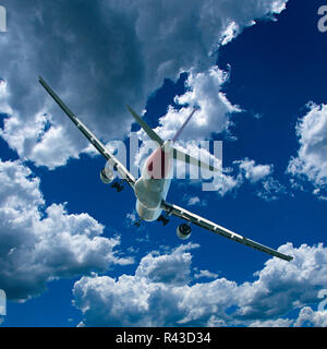 An artistic skyscape view of a commercial passenger jet aircraft flying in a vibrant blue sky, with bright white coloured Cumulus clouds. - Stock Photo