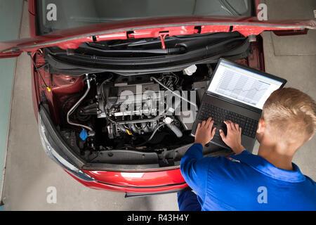 Mechanic Examining Car Engine With Help Of Laptop - Stock Photo