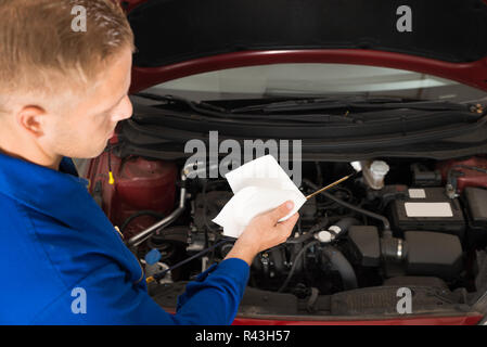 Mechanic Checking Oil Level In Car Engine - Stock Photo