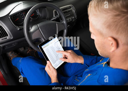 Mechanic Sitting In Car Looking At Digital Tablet - Stock Photo