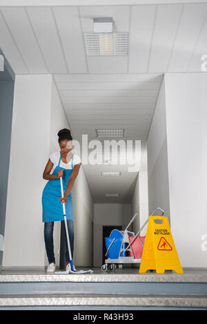 Woman Mopping Corridor - Stock Photo