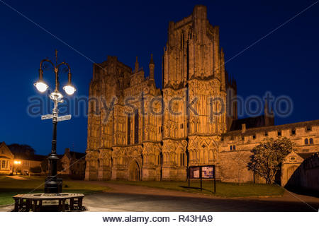 Night time image of  an illuminated Wells Cathedral with a lamppost and bench in front, Wells, Somerset, England, UK - Stock Photo