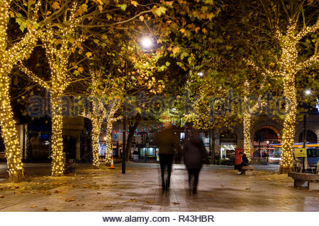 Evening image of a couple walking among trees decorated with Christmas lights and lamppost illuminating the pavement, Salisbury, Wiltshire England UK - Stock Photo