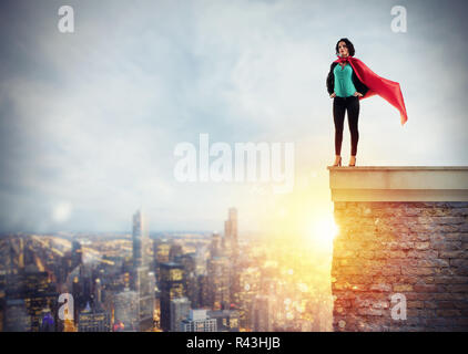 Successful businesswoman acts like a super hero above the roof of a building. Concept of determination and success - Stock Photo