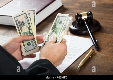 Corrupt Judge Counting Money At Desk - Stock Photo