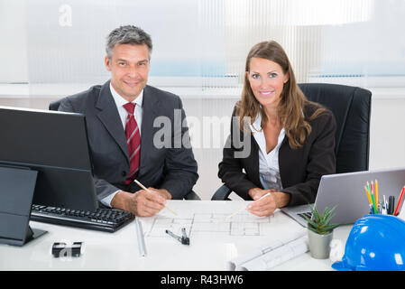 Two Architects Discussing Blueprint In Office - Stock Photo