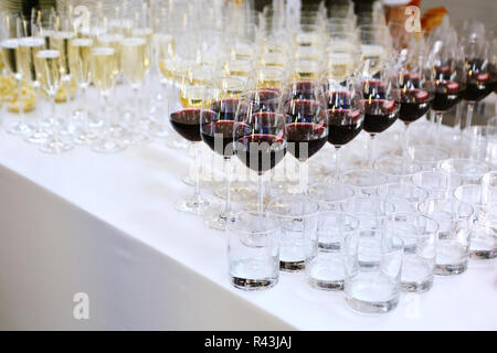 Glasses of red wine in a row on white table - Stock Photo