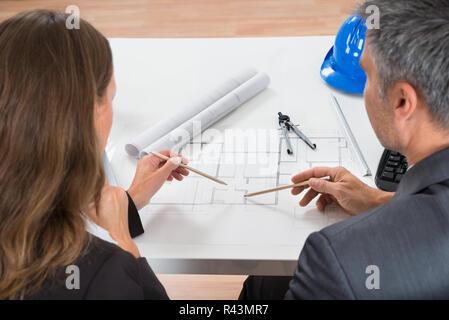 Two Businesspeople Working On Blueprint - Stock Photo